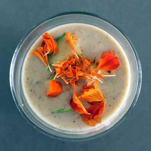 koud soepje van komkommer en druiven gegarneerd met afrikaantjes