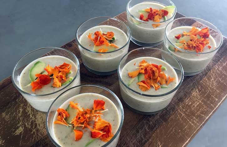 koude soep van komkommer en druiven gegarneerd met bloemen