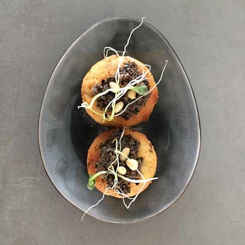 glutenvrije cake van amandelmeel en parmezaanse kaas gegarneerd met olijvenjam